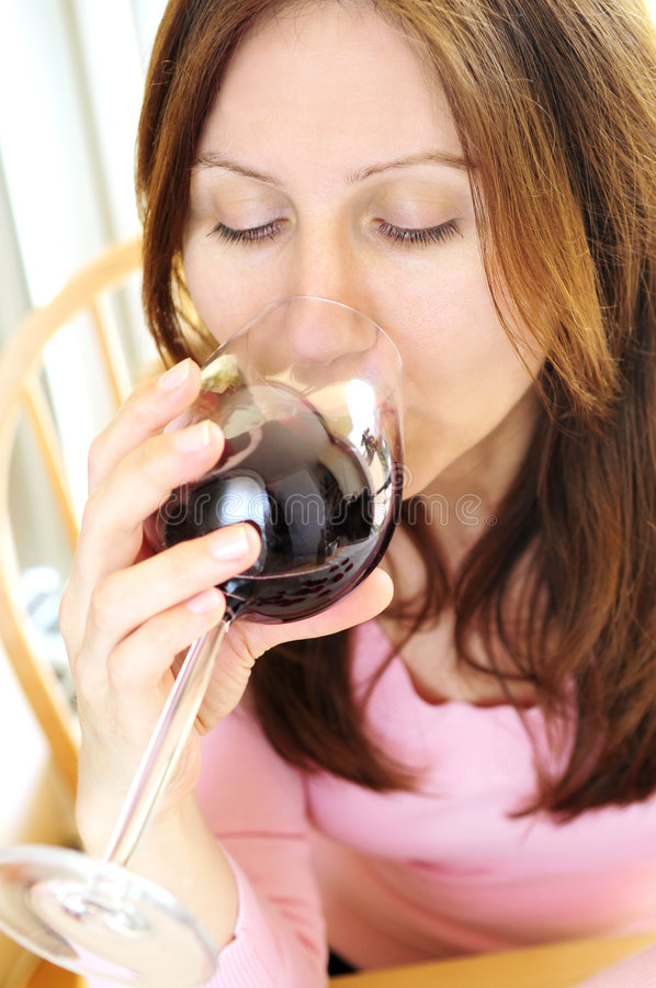 Mature woman with a glass of red wine stock images