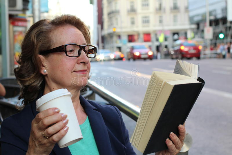 Mature woman with glasses drinking coffee and reading book sitting indoor in urban cafe. Cafe city lifestyle with traffic lights. In the background stock photography