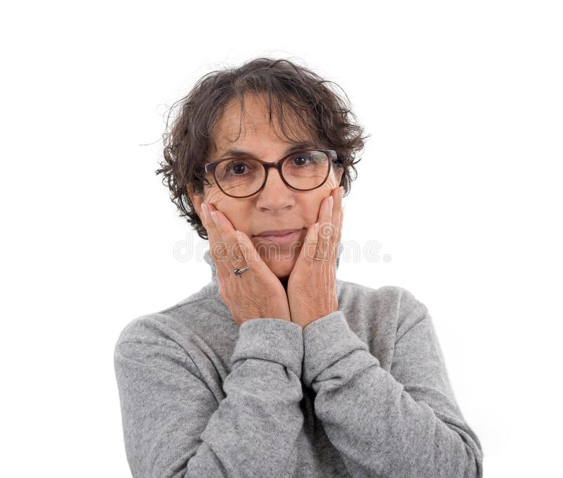 Mature woman with hands on her face stock image