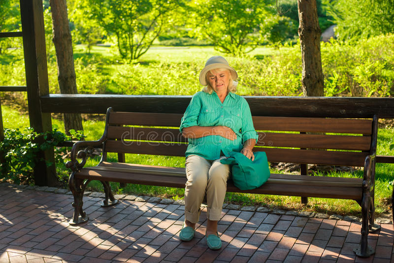 Mature woman has stomach ache. stock photography