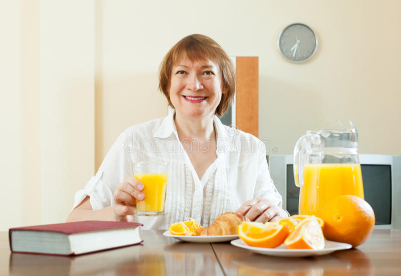 Mature  Woman Having Breakfast With Book Royalty Free Stock Photo