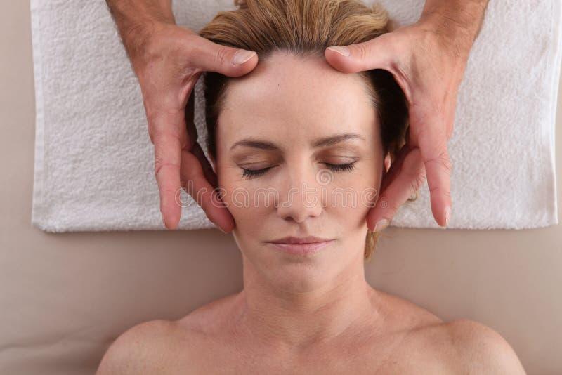 Mature woman having facial massage royalty free stock photos