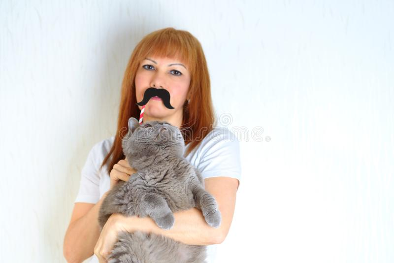 Mature woman having fun with a fake moustache and embracing pet. stock image
