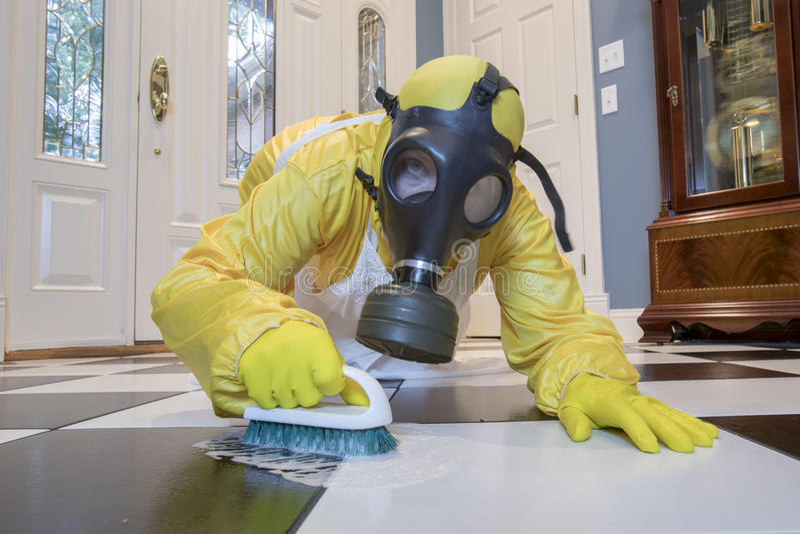 Mature woman in Haz Mat suit scrubbing floor with brush stock images
