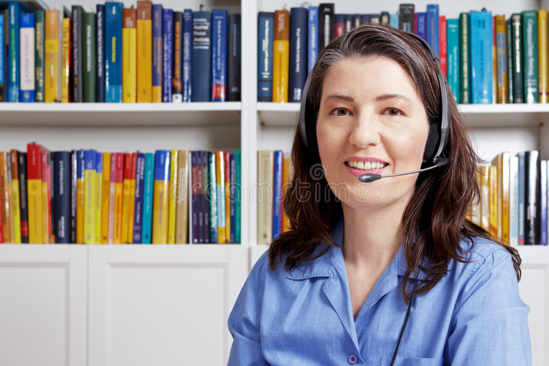 Mature woman headset copy space. Friendly middle aged woman with headset and a blue shirt in front of lots of books, talking to a customer via the internet stock image