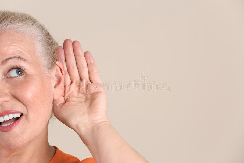 Mature woman with hearing problem stock images