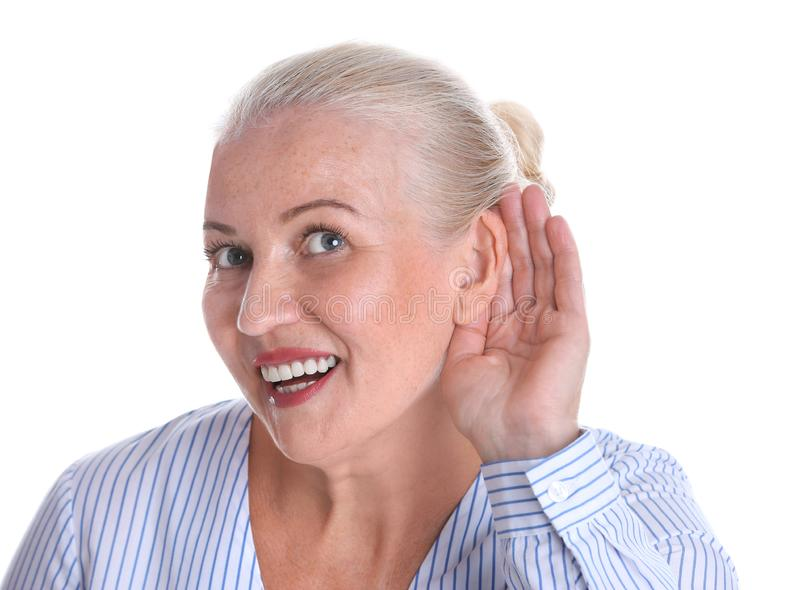 Mature woman with hearing problem on white. Background stock images