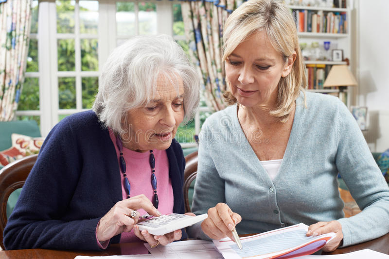 Mature Woman Helping Senior Neighbor With Home Finances royalty free stock photos