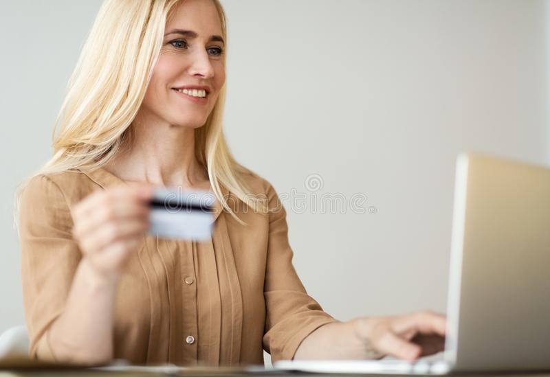Mature Woman Holding Credit Card And Purchasing Online royalty free stock image