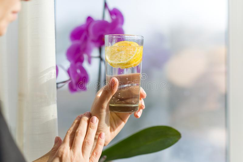 Mature woman is holding a glass with healthy drink. Natural antioxidant water with lemon, female stands near a window, enjoys drin. K royalty free stock photo