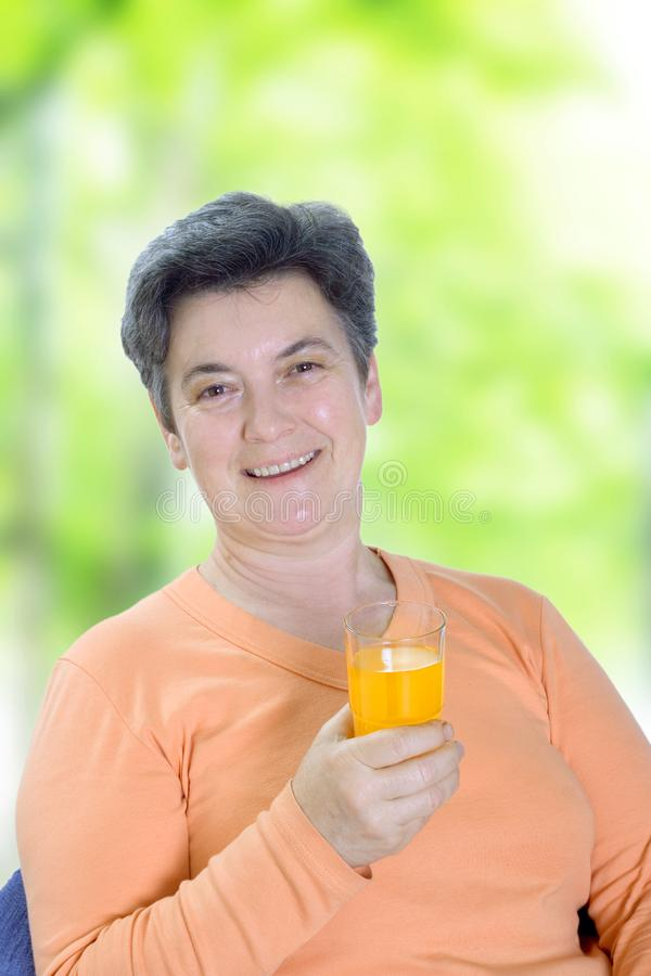 Mature woman holding glass of juice royalty free stock image