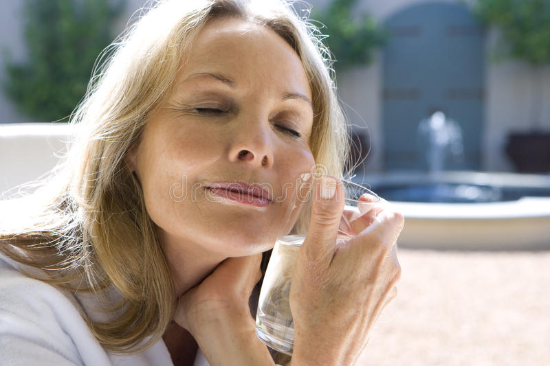 Mature woman holding glass of water to face, eyes closed, close-up royalty free stock photos