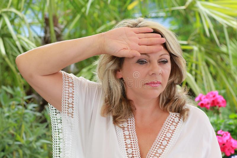 Mature woman holding her hand at her forehead. Middle age woman with dizziness hloding her hand at her forehead stock image