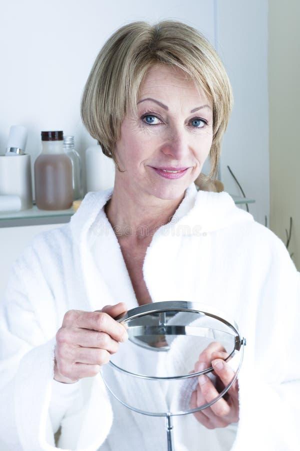 Mature woman holding mirror