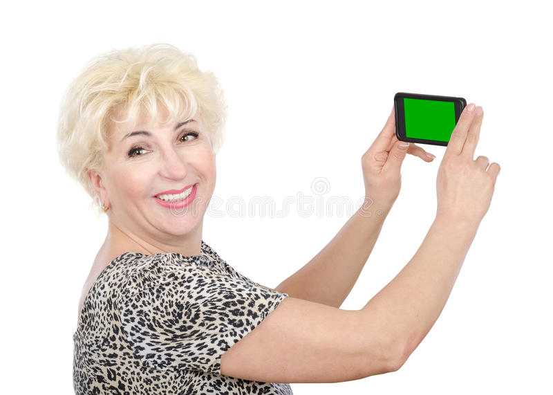 Mature woman holds cellphone with chroma key screen. Cheerful blonde middle aged woman captures photo by mobile phone with green screen. Side view of woman in stock images