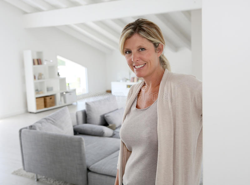 Mature woman at home welcoming guests at front door stock images