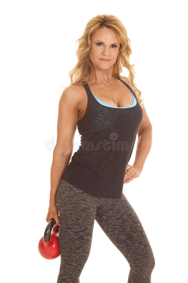 Mature woman kettle bell down one hand. A mature woman is standing in a black tank top with a kettle bell in her hand stock photography