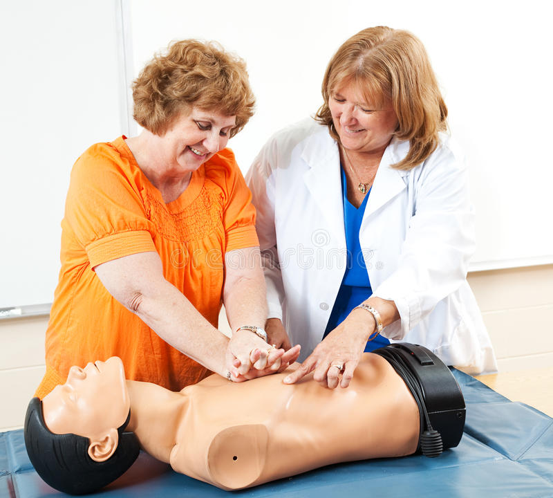 Mature Woman Learning CPR. Adult education student learning CPR first aid with the help of a doctor or nurse stock photo
