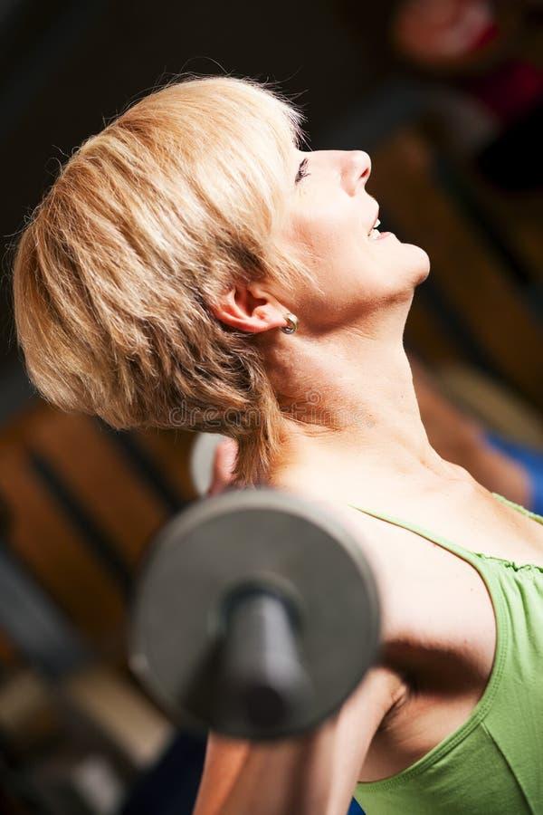 Mature woman lifting barbell