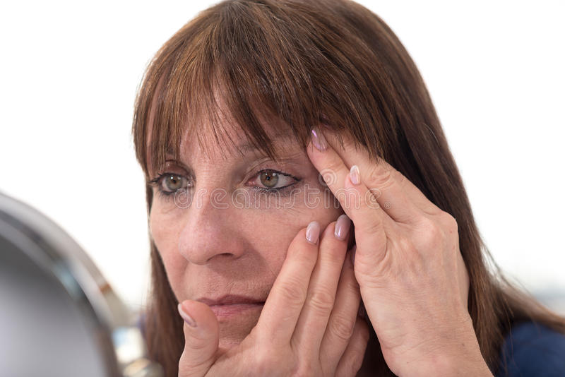 Mature woman looking at her eye wrinkles royalty free stock photos