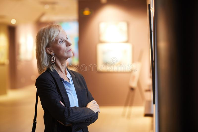 Mature Woman Looking at Paintings in Art Gallery stock image