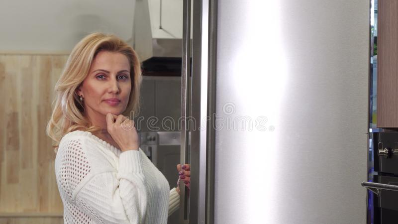 Mature woman looking thoughtfully into the fridge picking food stock photos