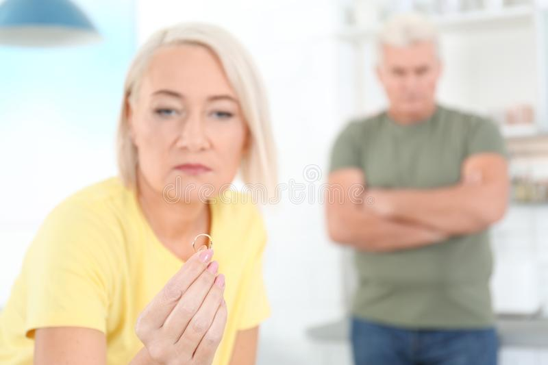 Mature woman looking on wedding ring after conflict with her husband at home royalty free stock images