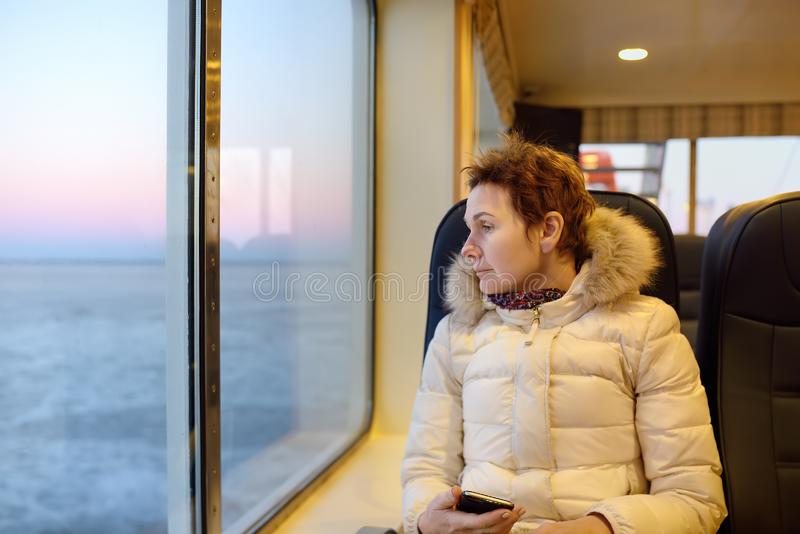 Mature woman is looking on the window at the amazing view of frozen sea during crossing on the ferry boat. Sea travel in winter stock images