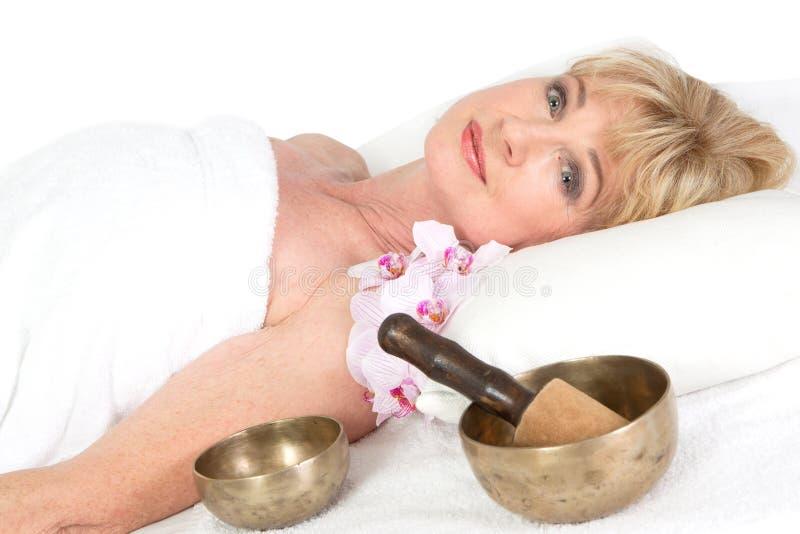 Mature woman lying on massage table stock image