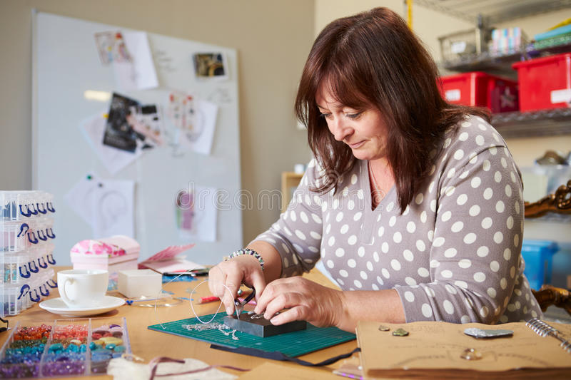Mature Woman Making Jewelry At Home royalty free stock photo