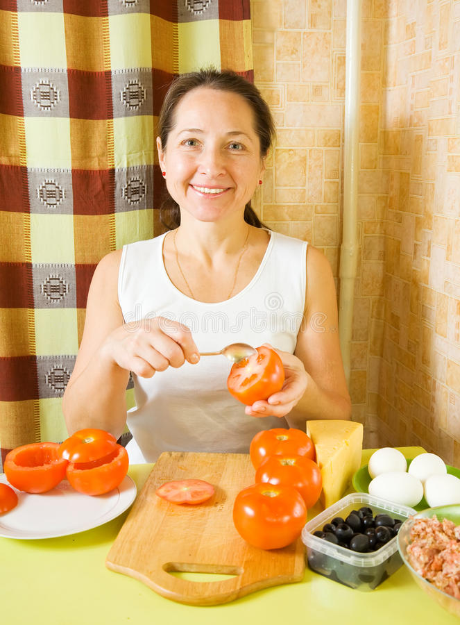 Mature woman making stuffed tomato. In her kitchen. See in series stages of cooking of farci tomato stock image