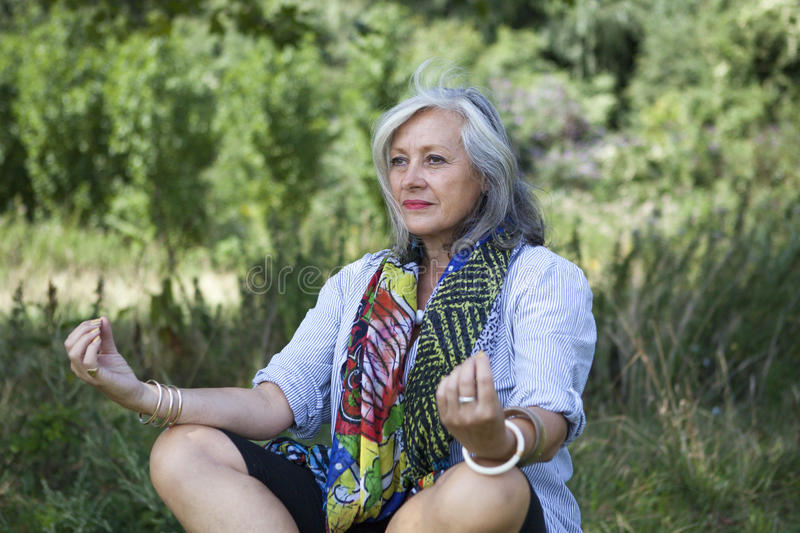 Mature woman meditating royalty free stock photos