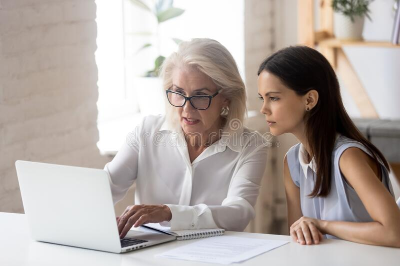 Mature woman mentor explain intern corporate application seated at desk royalty free stock photography