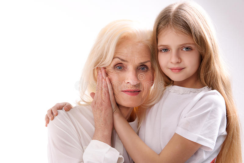 Mature woman near her granddaughter. Old lady is beside small female grandchild. They are smiling and looking at camera. Isolated. Copy space royalty free stock photo