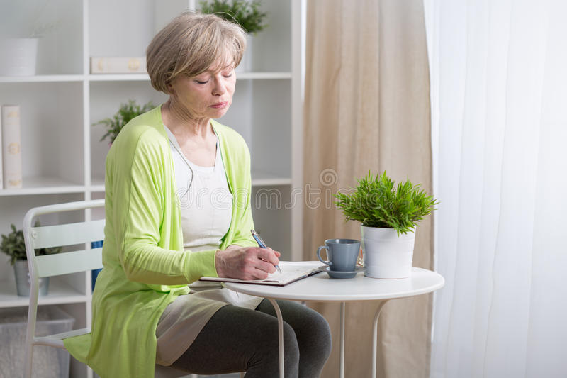 Mature woman noting in calendar royalty free stock image