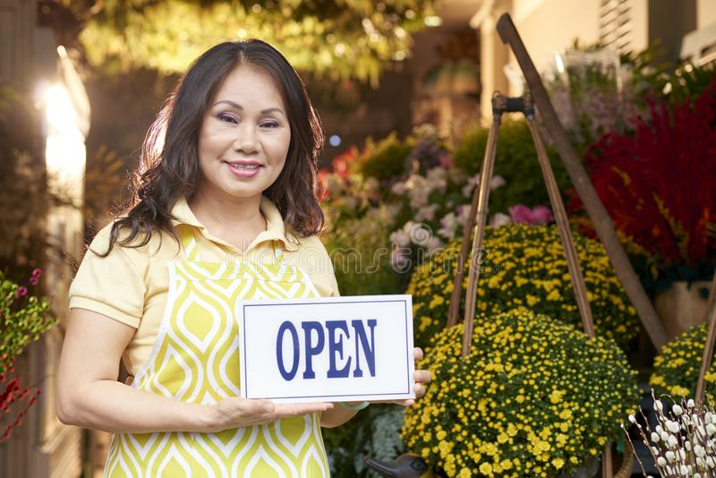 Mature woman opening flower shop stock photography