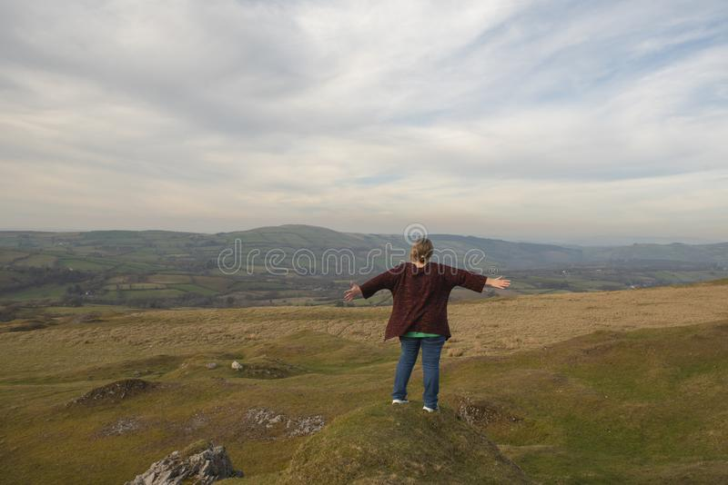 Mature woman with outstretched arms overlooking view stock photo