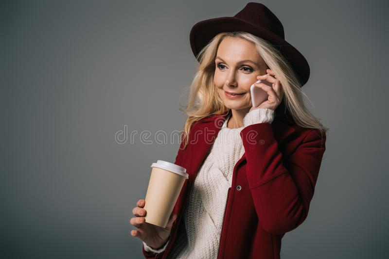 Mature woman with paper cup of coffee talking by phone. On grey royalty free stock photo