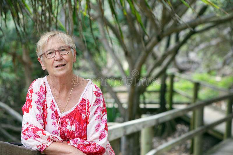 Mature woman in park. Beautiful smiling mature woman with white and red dress leaning on park's walkway handrail royalty free stock photography