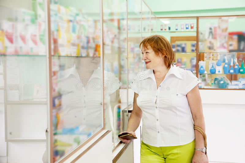 Mature woman in pharmacy drugstore. Mature woman near counter in pharmacy drugstore royalty free stock photography