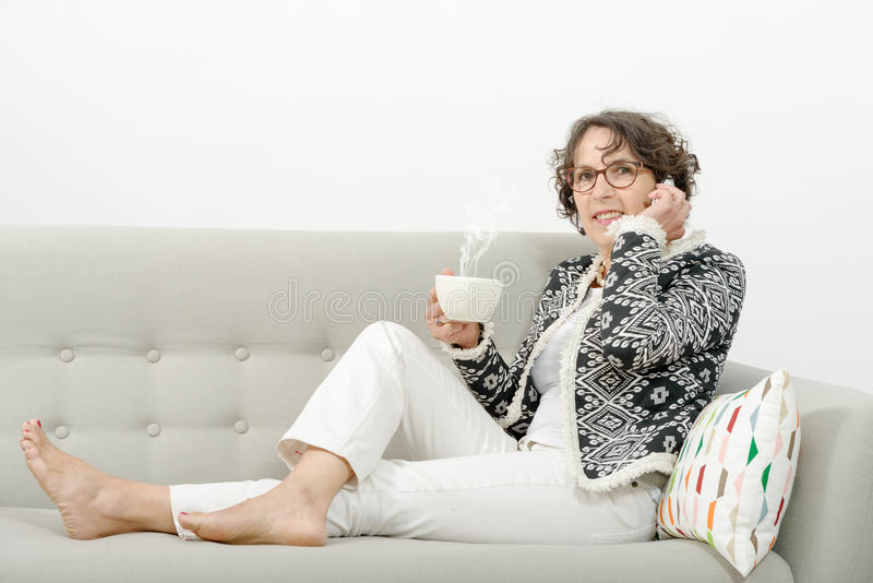 Mature woman with phone, drinking tea stock image