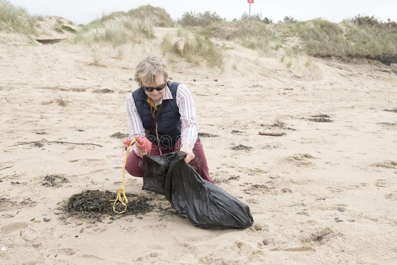 Mature woman picking up litter from a beach stock photo