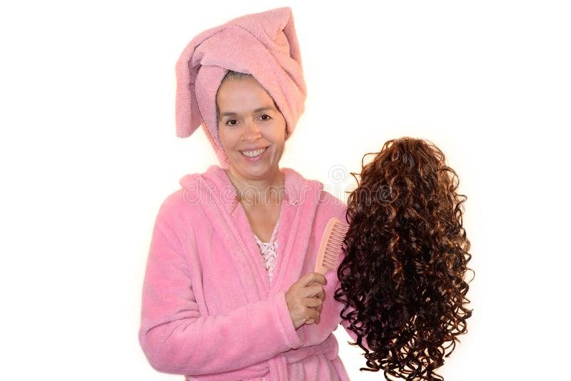 Smiling woman holding wig and comb Pink bathrobe. A mature woman in a pink bathrobe and pink towel on her head is holding a curly wig in a hand and a comb in the royalty free stock photos