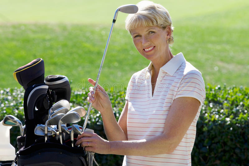 Mature woman playing golf, taking golf club from bag, smiling, side view, portrait royalty free stock image