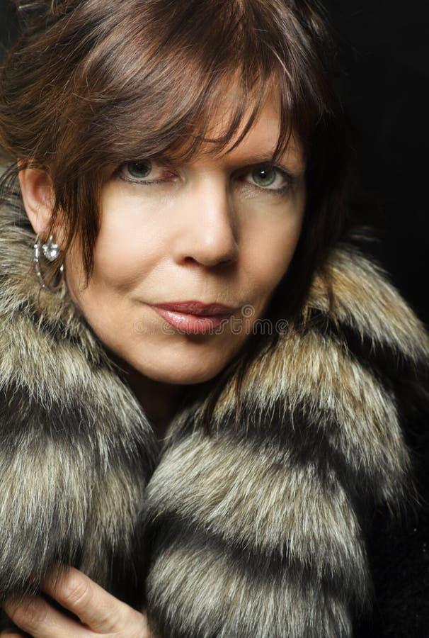 Mature woman portrait with fox fur stock image