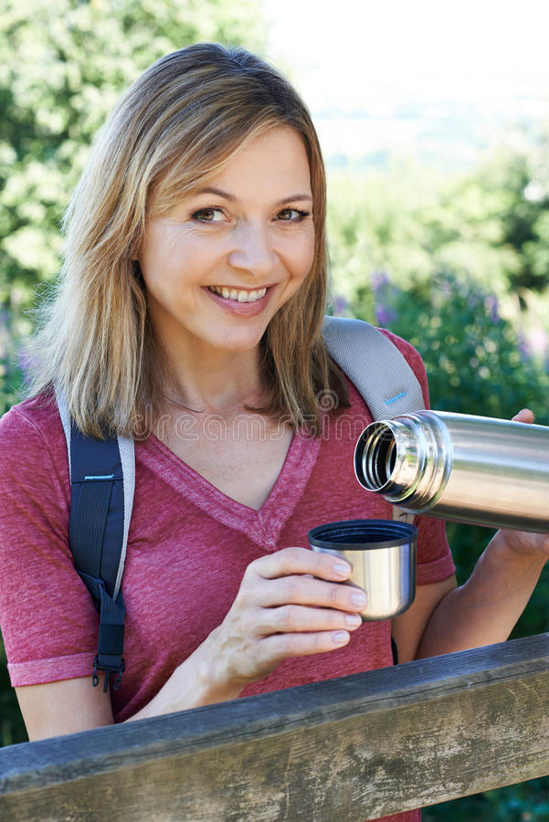 Mature Woman Pouring Hot Drink From Flask On Walk. Mature Woman Pours Hot Drink From Flask On Walk stock images