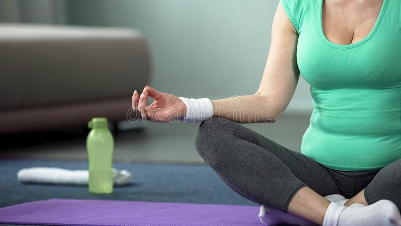 Mature woman practicing yoga poses at home close-up, meditation and health royalty free stock photography