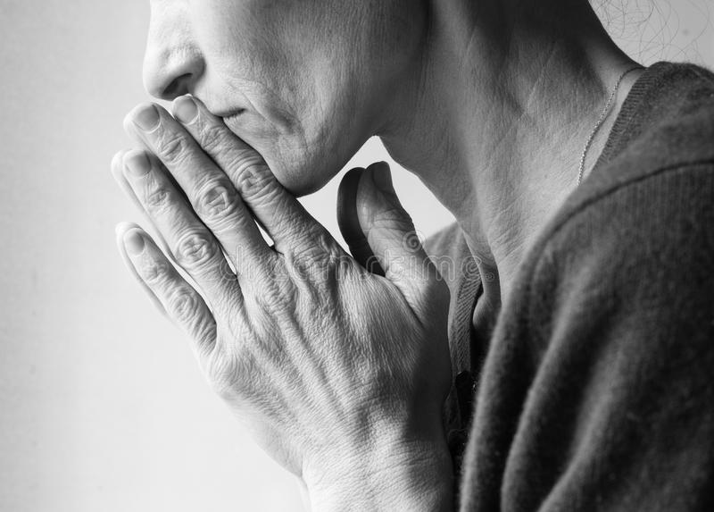 Mature woman praying (black and white) stock image