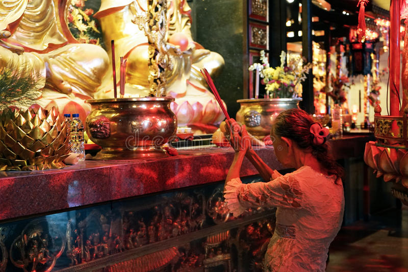 Mature Woman Praying in Buddhist Temple. Mature woman holding smoking incense sticks in Buddhist temple royalty free stock image