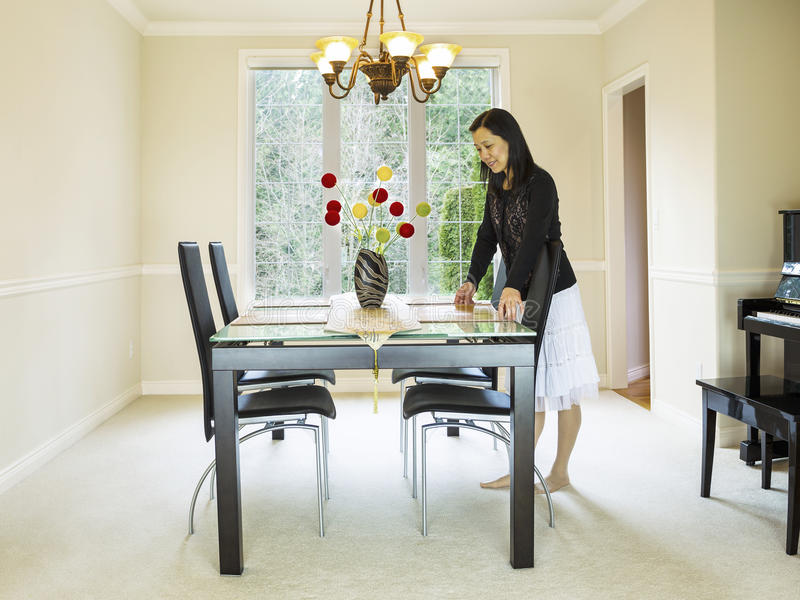 Mature woman preparing dining room table. Photo of mature woman placing diner mats in family formal dining room table with daylight coming through large windows royalty free stock image